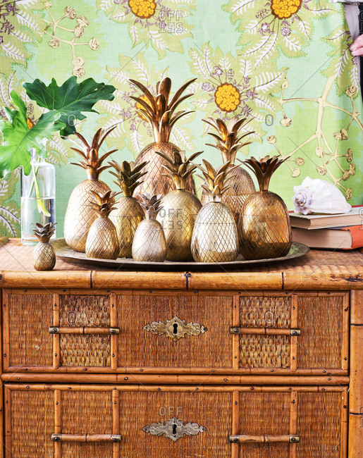Copper pineapples on wicker dresser