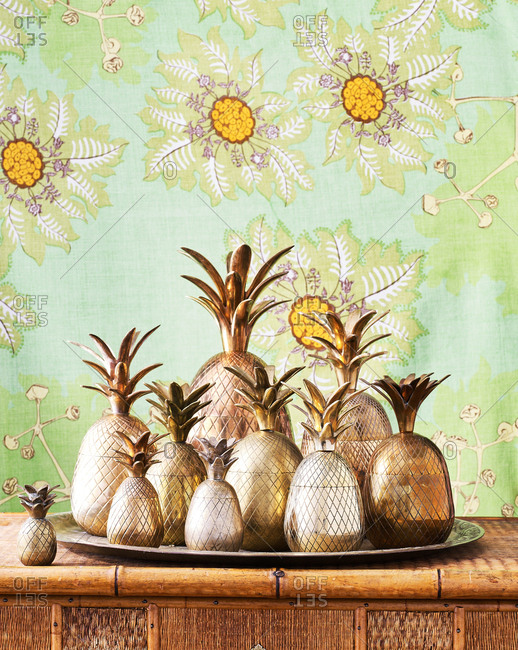 Copper pineapples on a wicker dresser