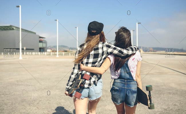 Back view of two young women with longboards walking arm in arm on beach promenade