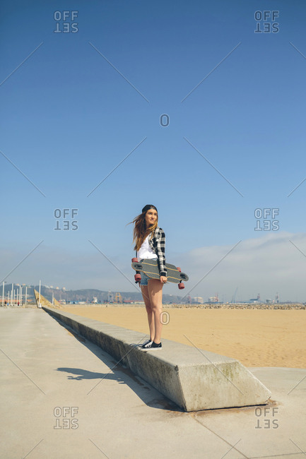 Young woman with longboard standing on a wall at beach promenade