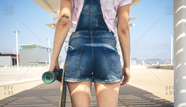 Back view of young woman with longboard on beach promenade- partial view