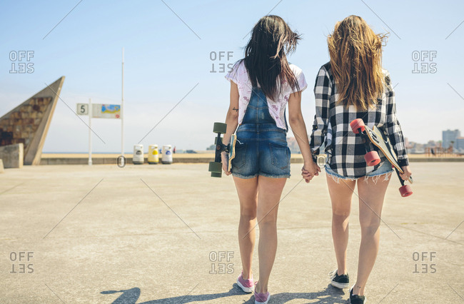 Back view of two young women with longboards walking hand in hand on beach promenade