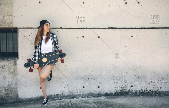 Portrait of happy young woman with longboard standing in front of concrete wall