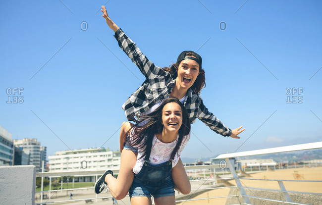 Young woman giving her friend a piggyback ride on roof terrace
