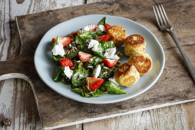 Plate of spinach salad with falafel- goat cheese- strawberries and sunflower seed