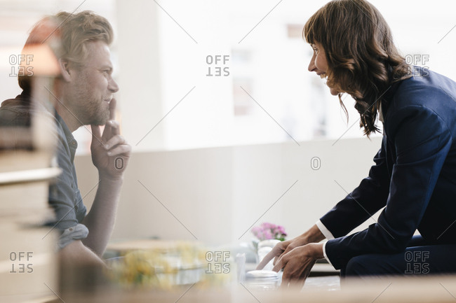 Man and woman sitting in cafe- discussing vividly