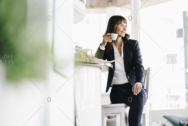 Businesswoman sitting in cafe- drinking coffee