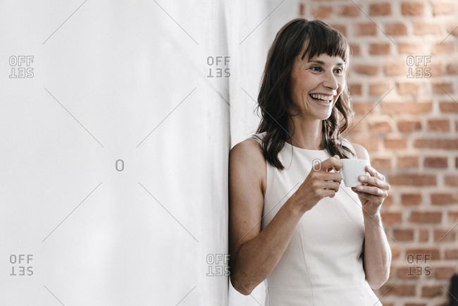 Woman drinking coffee in office- leaning against wall