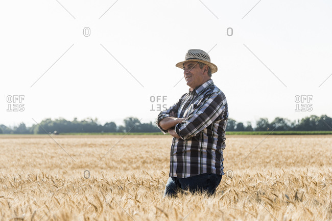 Smiling senior farmer standing in a field