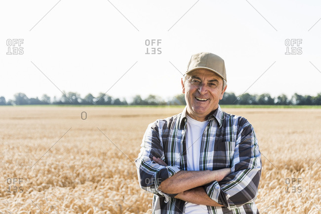 Portrait of laughing senior farmer standing in front of a field