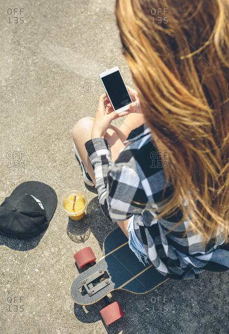 Back view of young woman with long hair looking sitting on longboard looking at smartphone
