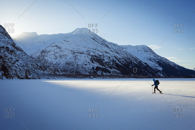 Woman snowshoeing across frozen Portage Lake