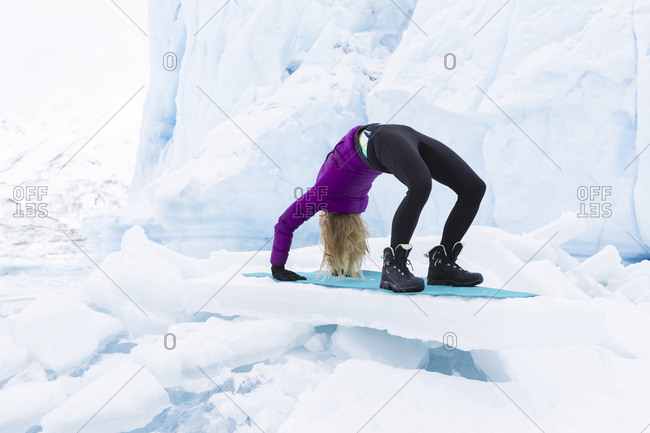Young woman in winter clothes doing the upward bow or wheel yoga pose in front of Portage Glacier in the winter
