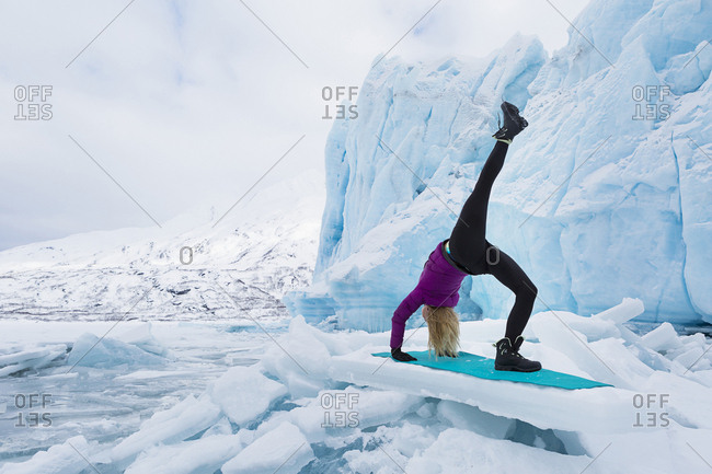 Young woman in winter clothes doing the one legged upward bow or wheel yoga pose in front of Portage Glacier in the winter