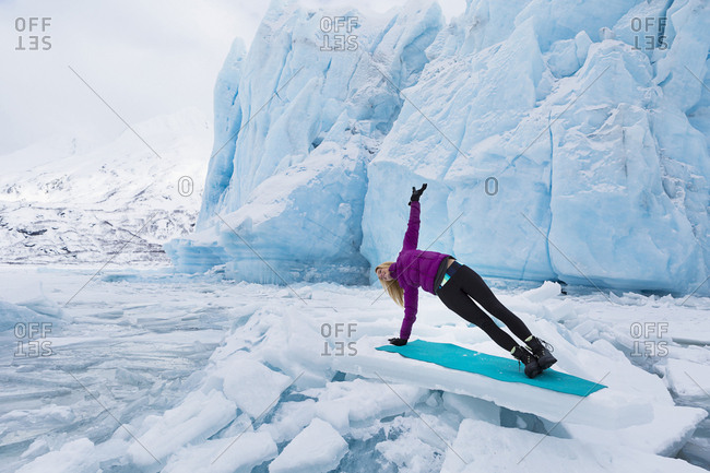 Woman in winter clothes doing the side plank yoga pose in front of Portage Glacier in the winter