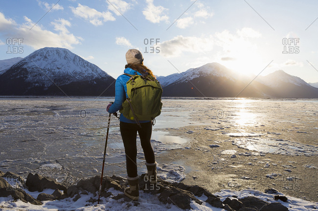 Young woman watching the setting winter sun while overlooking ice flows