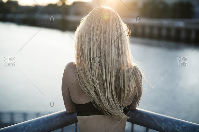 A female fitness model looks over a railing towards the sunset in an urban environment.