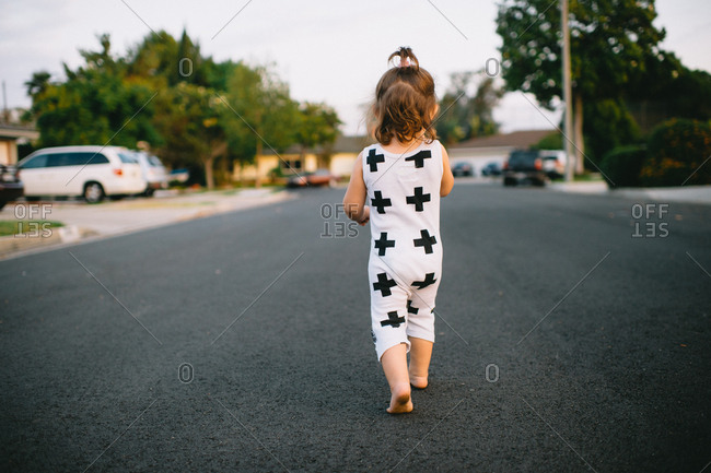 Rear view of a toddler girl walking in the street