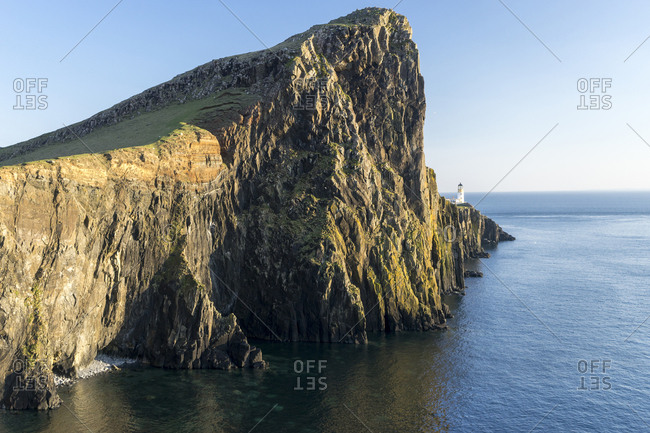 Majestic cliff by sea against clear sky