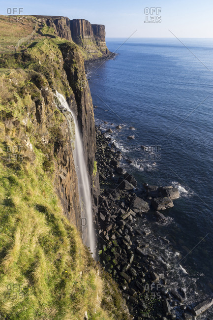 Waterfall on majestic cliff by sea