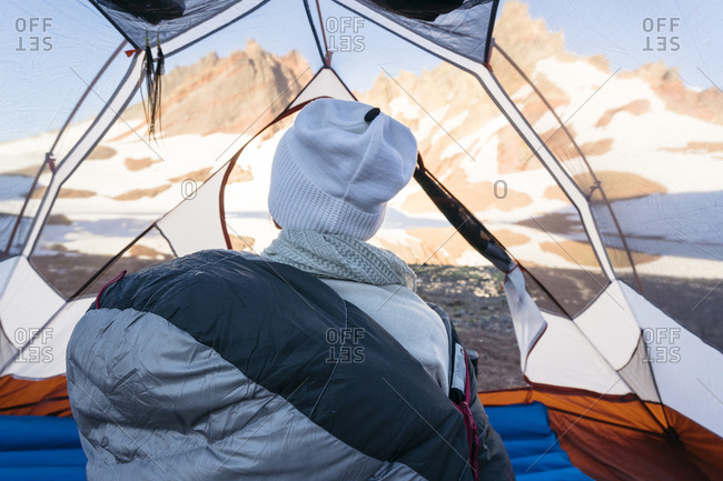 Rear view of hiker looking at view while sitting in tent