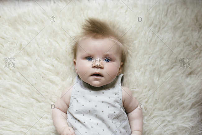 Overhead portrait of cute baby girl lying on furry rug at home
