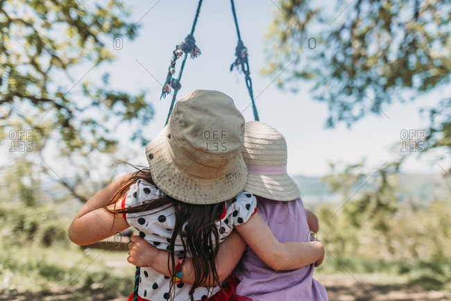 Rear view of sisters wearing hats sitting on rope swing