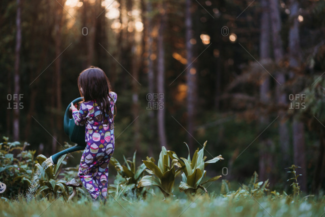 Rear view of girl watering plants at garden