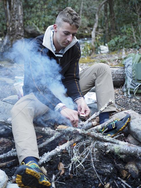 Hiker lighting up campfire at Pisgah National Forest