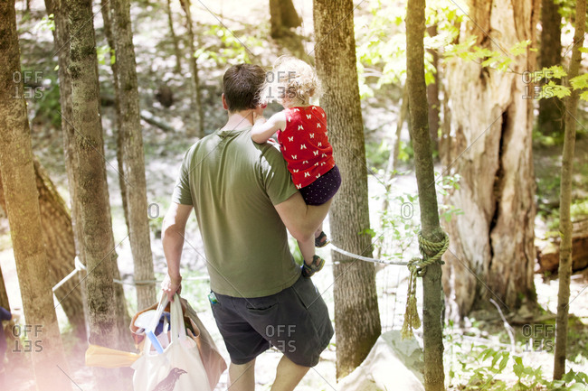 High angle view of father carrying daughter and bags while walking in forest