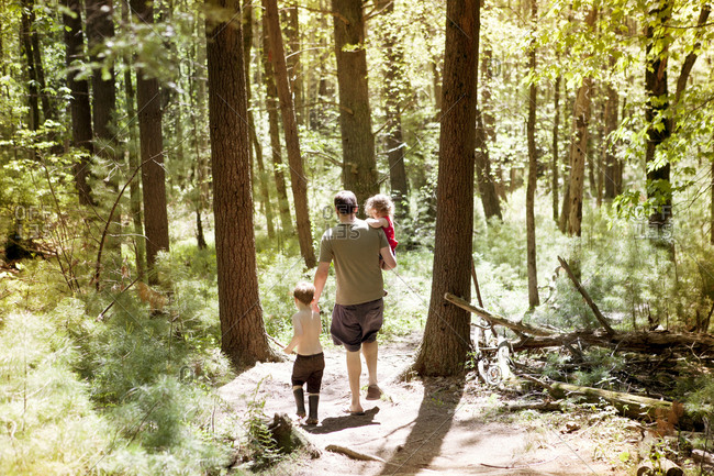 High angle view of father with son and daughter walking on dirt road amidst forest