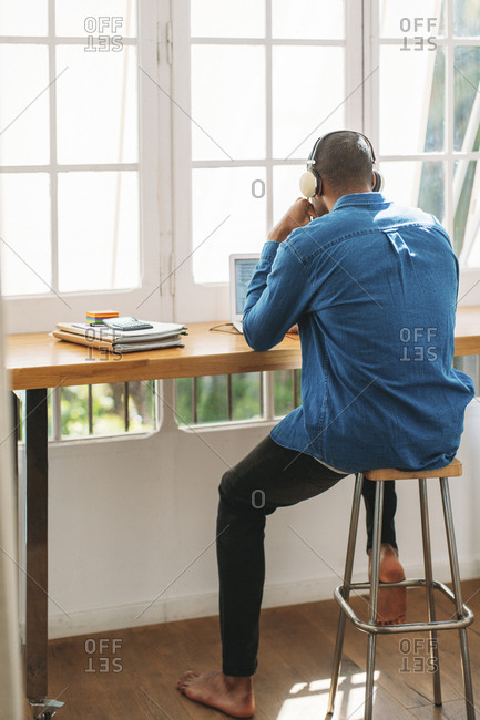 Full length rear view of man working at home office by window