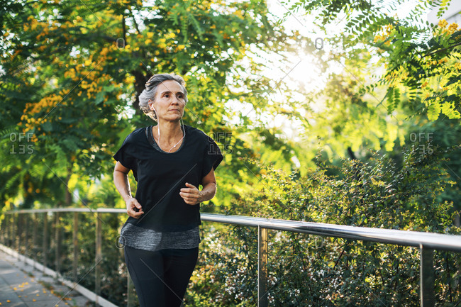 Woman looking away while jogging on footpath