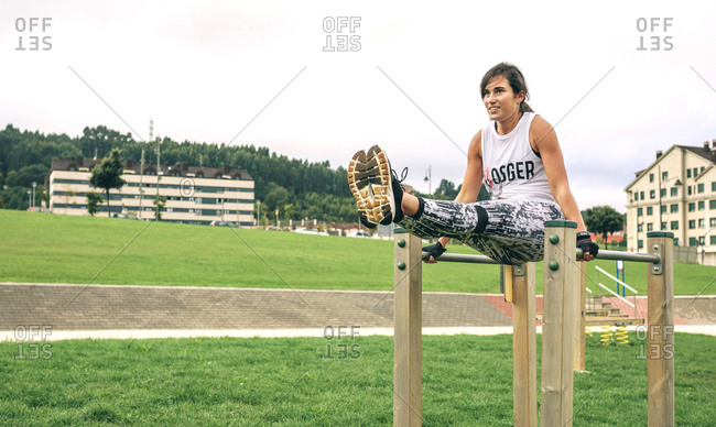 Full length of woman exercising on parallel bars at park
