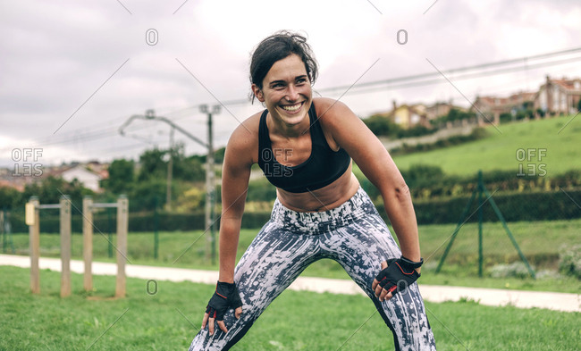 Happy sportswoman bending while exercising at park
