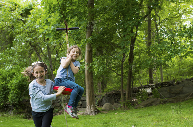 Happy sisters playing with zip line at park
