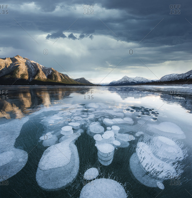 Majestic view of methane bubbles in Abraham Lake by mountains against stormy cloudy