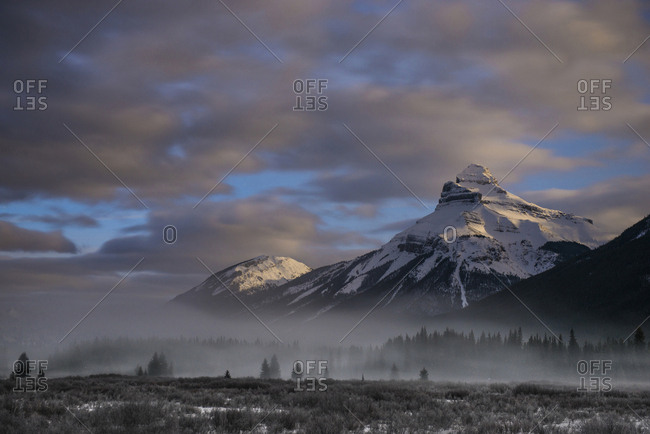 Scenic view of snowcapped mountains against stormy clouds at Icefields Parkway