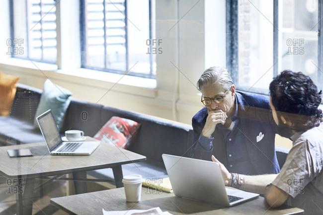 Businessmen discussing over laptop computer seen through window