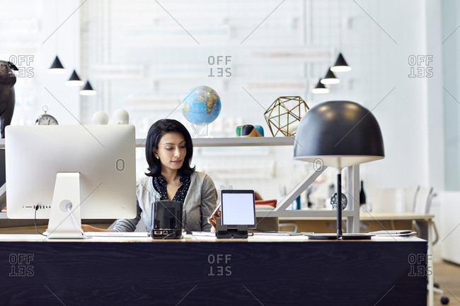 Businesswoman looking at smart phone while working in creative office