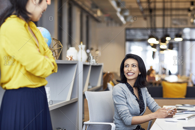 Happy businesswoman looking at female colleague while sitting in creative office