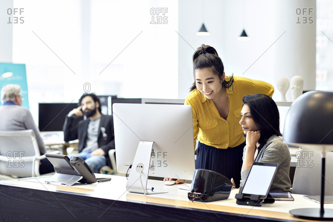Businesswomen working on desktop computer with male colleagues sitting in back ground