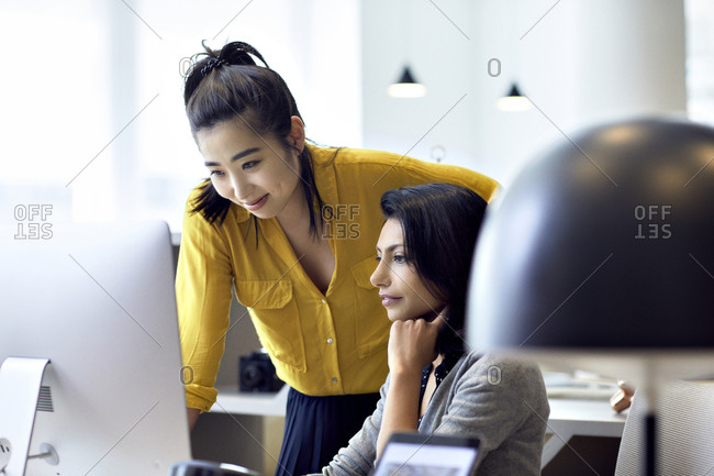 Businesswomen looking at desktop computer while working in office