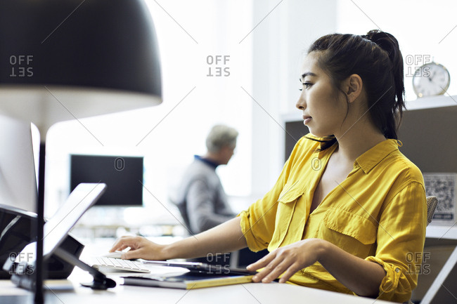 Businesswoman working on desktop computer with male colleague sitting in background