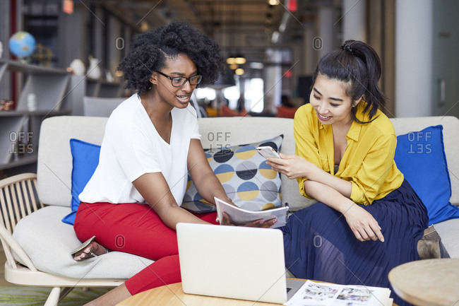 Businesswomen looking at file while sitting on sofa in creative office