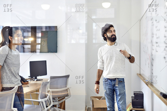 Business people looking at white board in creative office seen through window