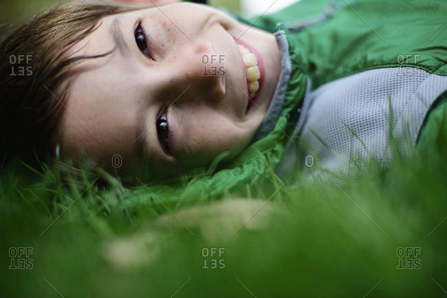 Portrait of happy boy lying on grassy field