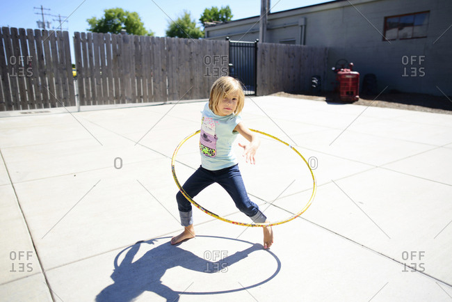 Portrait of girl playing with hula hoop at playground during summer
