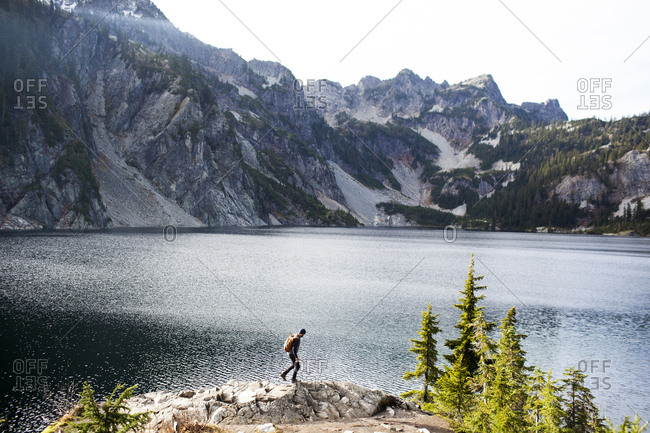 Side view of hiker walking on rocks by Snow Lake