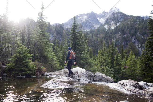 Hiker and dog walking on rocks by Snow Lake against mountains